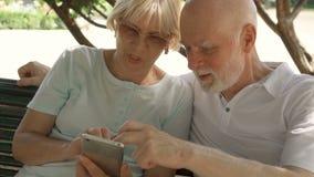 享受假期的愉快的家庭在欧洲 前辈坐长凳在浏览在智能手机的公园 股票录像