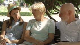 享受假期的愉快的家庭 前辈和他们的女儿坐在公园放松的长凳 股票视频