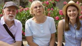 享受假期的愉快的家庭 前辈和他们的女儿坐在街道放松的长凳 股票录像