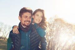 享受公司彼此的嬉戏的年轻爱恋的夫妇外面 免版税库存照片