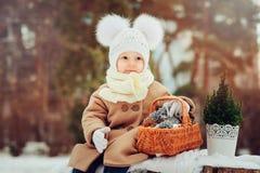 享受冬天步行的逗人喜爱的女婴在多雪的公园,佩带的温暖的帽子 免版税库存图片