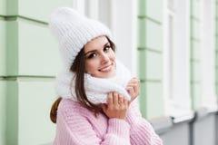 享受冬天的一名年轻微笑的妇女的特写镜头面孔戴被编织的围巾和帽子 库存图片
