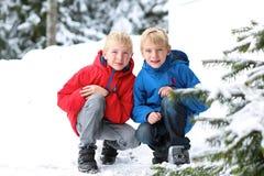 享受冬天滑雪假期的两个男孩 图库摄影