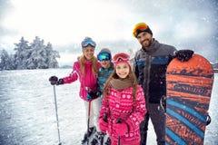 享受冬季体育和假期在雪的家庭在山 免版税库存照片