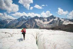 享受冰川步行的秀丽的在冰川的女性登山家在起重吊钩和太阳镜 反对 免版税库存照片