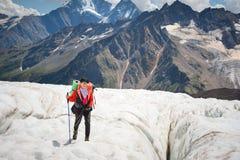 享受冰川步行的秀丽的在冰川的女性登山家在起重吊钩和太阳镜 反对 库存照片