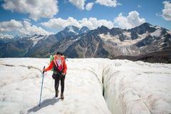 享受冰川步行的秀丽的在冰川的女性登山家在起重吊钩和太阳镜 反对 免版税图库摄影
