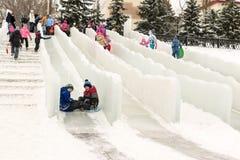 享受冰幻灯片的俄国家庭 库存照片