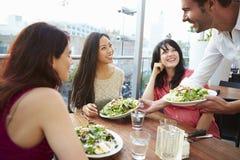 享受午餐的三个女性朋友在屋顶餐馆 免版税库存图片