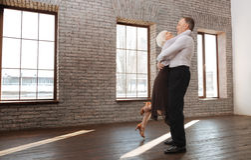 享受华尔兹的高兴退休的夫妇在舞蹈演播室 免版税图库摄影