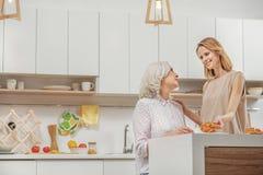 享受友好的谈话的愉快的家庭在厨房里 免版税库存照片