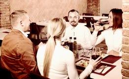 享受可口膳食的朋友在国家餐馆 免版税库存图片