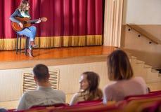 享受吉他音乐会的大量观众在音乐厅里 图库摄影