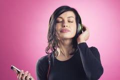 享受听到与耳机的音乐的微笑的镇静女孩 免版税库存照片