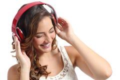 享受听到从耳机的音乐的年轻愉快的妇女 免版税库存图片