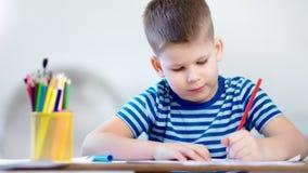 享受启发的体贴的矮小的逗人喜爱的男孩画创造性的图片使用红色铅笔 影视素材
