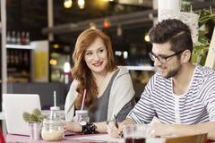 享受咖啡休息的自由职业者的夫妇 免版税图库摄影