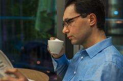 享受咖啡和一些新闻的业余时间 商人读书报纸,当喝杯子热的牛奶茶时 免版税库存图片