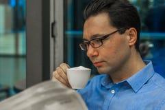 享受咖啡和一些新闻的业余时间 商人读书报纸,当喝杯子热的牛奶茶时 免版税图库摄影
