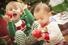 享受圣诞节早晨的混合的族种婴孩和新男孩   免版税库存照片