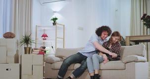 享受在一栋新的公寓的微笑和激动的夫妇时间在一坚硬移动的天以后他们采取从电视的遥控 股票录像