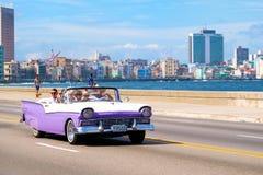 享受在一辆经典汽车的游人乘驾在Malecon avenu 免版税图库摄影
