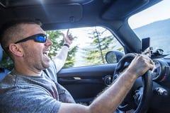 享受在他的汽车的愉快的人一次旅行在一个晴天 免版税图库摄影