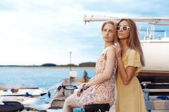 享受在口岸的两个女朋友晚上日落 图库摄影