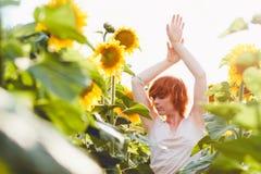 享受在向日葵在日落,美丽的红发妇女女孩的画象的领域的少女自然有的向日葵 库存图片