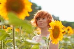 享受在向日葵在日落,美丽的红发妇女女孩的画象的领域的少女自然有的向日葵 库存照片
