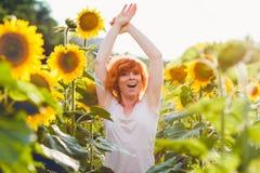 享受在向日葵在日落,美丽的红发妇女女孩的画象的领域的少女自然有的向日葵 免版税库存图片