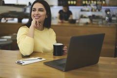 享受在咖啡店的女性自由职业者工作时间 免版税图库摄影