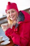 享受在咖啡馆的妇女热饮料在滑雪胜地 免版税库存照片