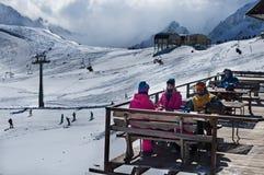 享受在咖啡馆的小组朋友热的饮料在滑雪胜地 库存照片