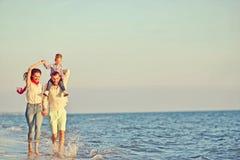 享受在夏天休闲的愉快的家庭和婴孩画象日落 免版税库存照片
