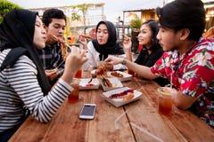 享受在室外的小组年轻朋友膳食 图库摄影