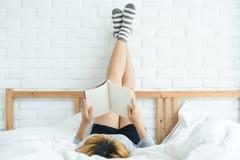 享受在家说谎在便衣的床阅读书乐趣的生活方式愉快的年轻亚裔妇女 图库摄影