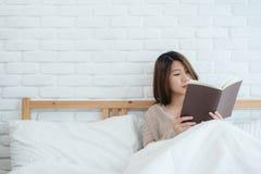 享受在家说谎在便衣的床阅读书乐趣的生活方式愉快的年轻亚裔妇女 免版税图库摄影