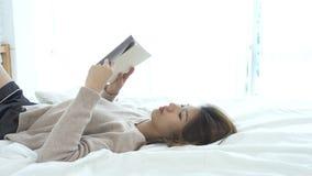 享受在家说谎在便衣的床阅读书乐趣的生活方式愉快的年轻亚裔妇女 影视素材
