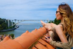 享受在屋顶的妇女sunbath在河桥梁背景 免版税库存图片