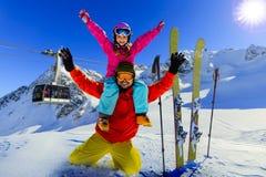 享受在山的愉快的家庭冬天假期 滑雪,太阳 免版税库存图片