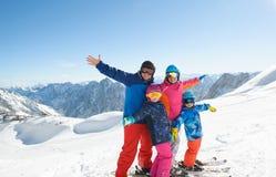 享受在山的愉快的家庭冬天假期 免版税图库摄影