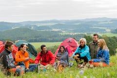 有帐篷和风景的坐的野营的朋友 免版税库存图片