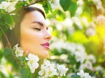 享受在开花的苹果树的美丽的少妇春天自然 免版税库存照片