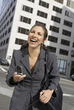 享受在手机的女实业家交谈户外 免版税库存图片