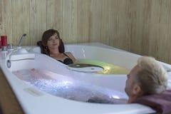 享受在极可意浴缸的年轻愉快的夫妇浴-恋人夫妇极可意浴缸水池的 免版税库存照片