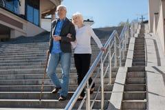 享受在正方形的年迈的夫妇步行 免版税库存图片