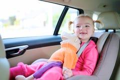 享受在汽车的愉快的小孩女孩安全旅行 库存图片