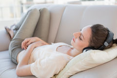 享受在沙发的轻松的偶然少妇音乐 库存照片