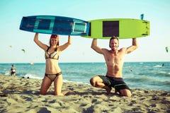 享受在沙滩的俏丽的微笑的夫妇kitesurfer夏令时 库存图片
